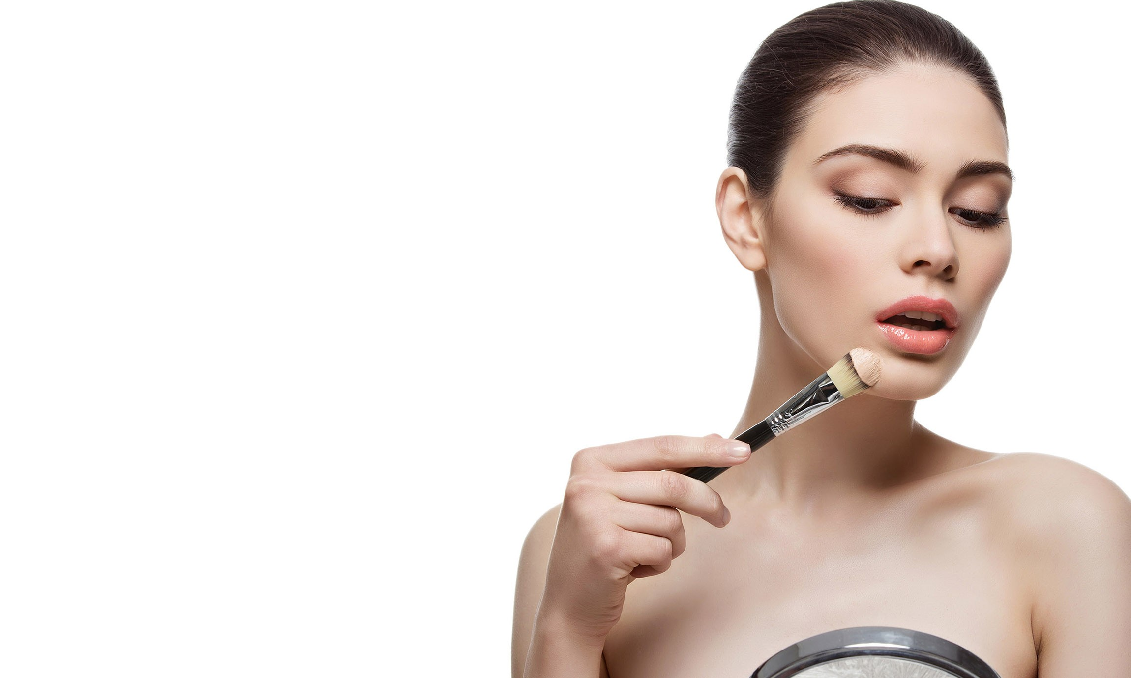 Beautiful young woman applying liquid foundation with brush. Isolated over white background. Copy space.